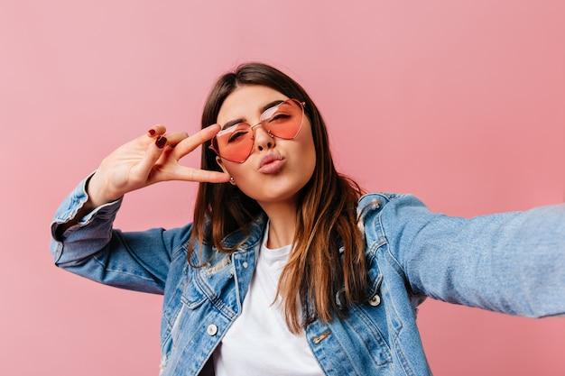 Jovem glamourosa tomando selfie em fundo rosa. menina morena atraente mostrando o símbolo da paz.