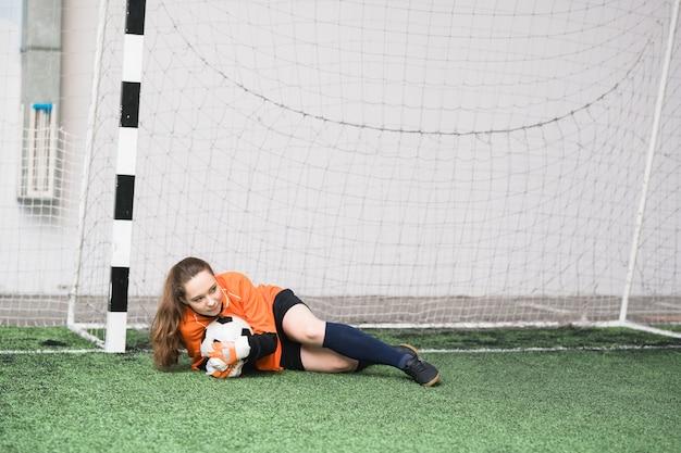Jovem goleira com uma bola de futebol deitada em um campo verde nos portões durante um jogo de futebol