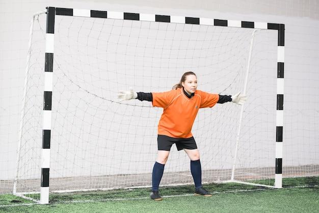 Jovem goleira com uniforme esportivo e luvas esticando os braços enquanto está no portão pronta para pegar a bola