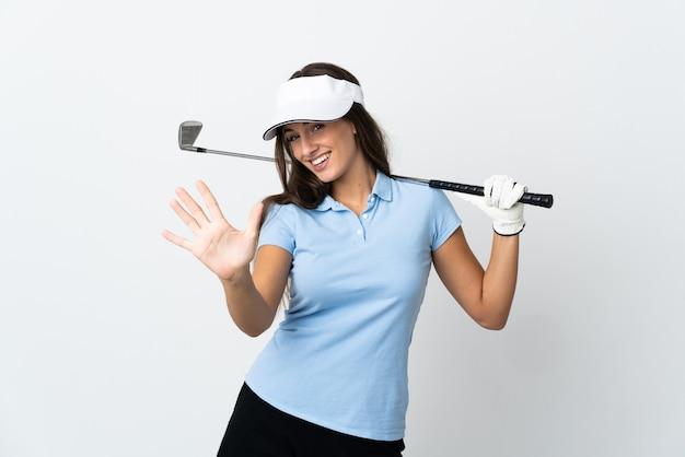 Jovem golfista isolada contando cinco com os dedos