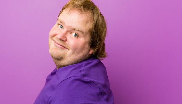 Jovem gordo ruiva autêntica olha de lado sorridente, alegre e agradável.