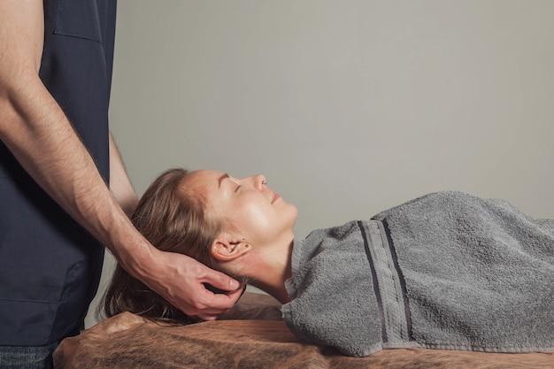 Jovem gosta de massagem de bem-estar esportiva no consultório médico da sala de fitness. o massagista profissional em casa faz exercícios de massagem. conceito de relaxamento, beleza, saúde, cuidados com o corpo. copie o espaço