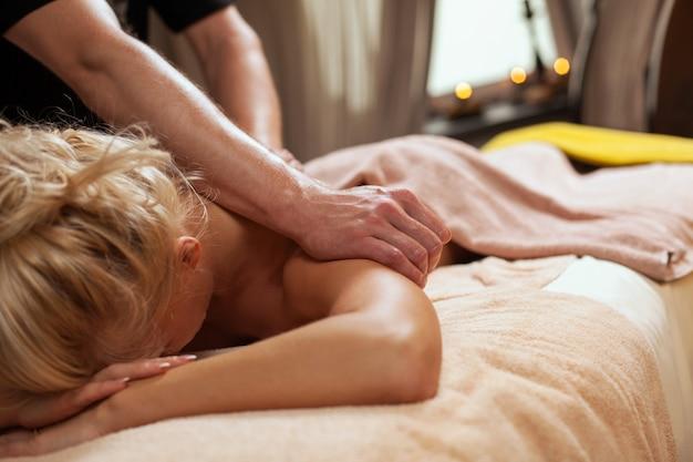 Jovem gosta de massagem em um spa