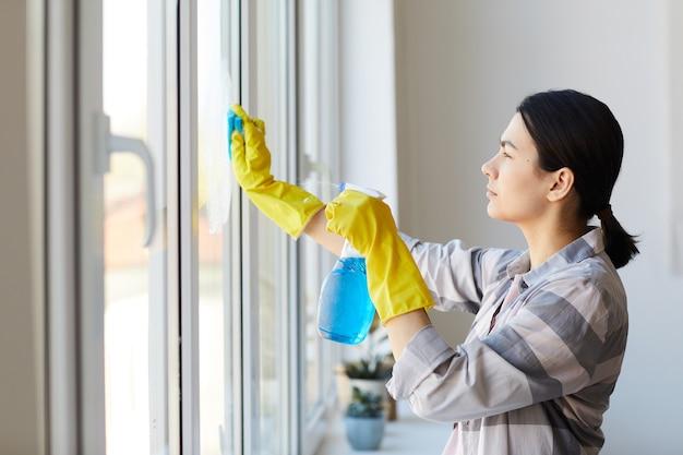 Jovem governanta em luvas de borracha usando spray de limpeza e esponja e limpando a janela