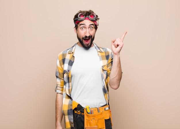 Jovem governanta se sentindo um gênio feliz e animado depois de realizar uma ideia, levantando o dedo alegremente, eureka! contra parede plana