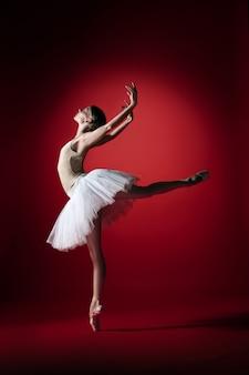 Jovem graciosa bailarina feminina ou bailarina clássica dançando no estúdio vermelho.