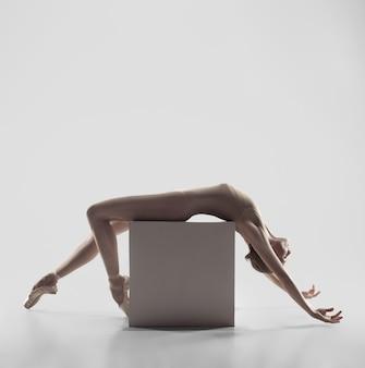 Jovem graciosa bailarina ou bailarina clássica dançando no estúdio branco
