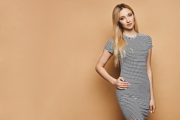 Jovem graciosa com corpo perfeito magro em vestido listrado na parede de pêssego com espaço de cópia à esquerda, isolado. menina bonita modelo com cabelos loiros em uma roupa de verão.