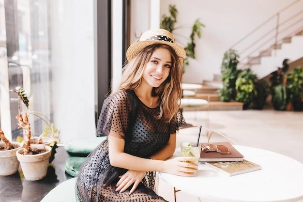Jovem graciosa descansando à mesa com um copo de chá frio e revistas