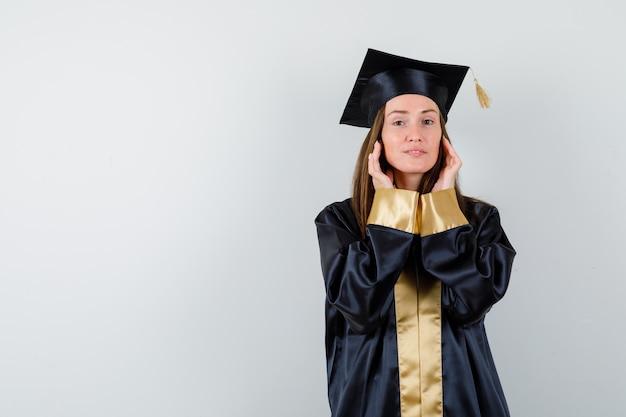 Jovem graduada em vestido acadêmico de mãos dadas nas bochechas e olhando confiante, vista frontal.