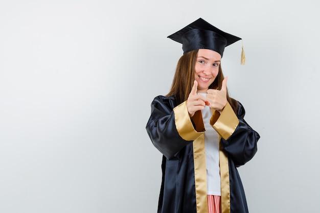Jovem graduada feminina aparecendo baque enquanto aponta para o lado em trajes acadêmicos e parece feliz. vista frontal.