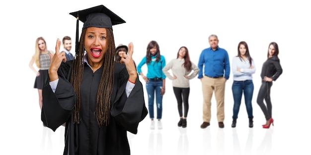Jovem graduada mulher negra usando tranças cruzando os dedos, deseja ter sorte para projetos futuros, excitado mas preocupado, expressão nervosa, fechando os olhos