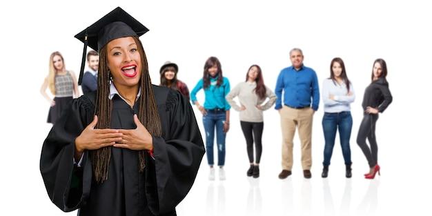 Jovem graduada mulher negra usando tranças fazendo um gesto romântico, apaixonado por alguém ou mostrando carinho por algum amigo