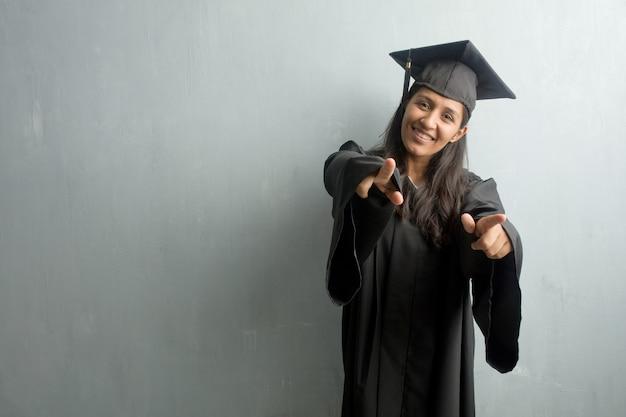 Jovem, graduado, indianas, mulher, contra, parede, alegre, apontar, dedos