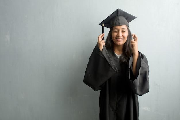 Jovem, graduado, indianas, mulher, contra, parede, cruzar, seu, dedos