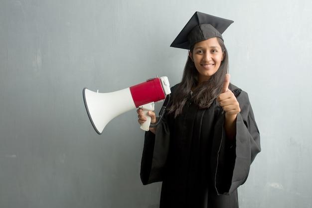 Jovem, graduado, indianas, mulher, contra, um, parede, alegre, e, excitado, sorrindo, e, levantando, dela