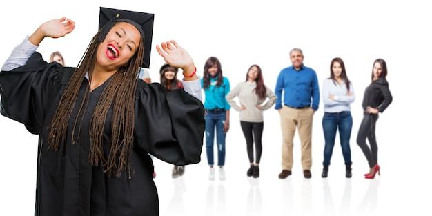 Jovem, graduado, mulher preta, desgastar, tranças, escutar música, dançar, e, tendo divertimento, em movimento, shouting, e, expressar, felicidade, liberdade, conceito