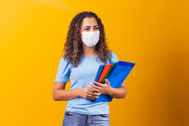 Jovem graduado ou estudante do ensino médio usando máscara cirúrgica contra o covid 19. novo conceito de normalidade e educação