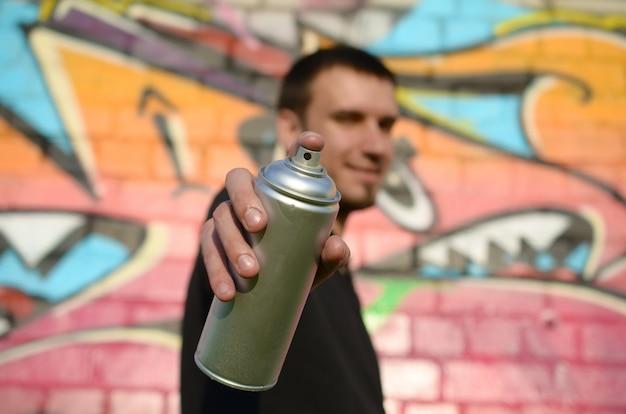 Jovem grafiteiro aponta sua lata de spray