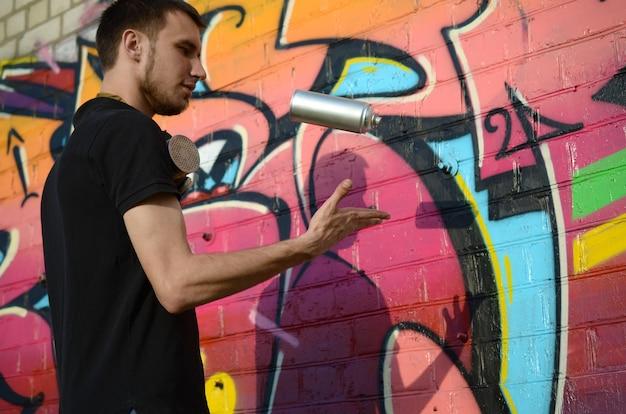 Jovem grafiteiro com máscara de gás no pescoço jogar sua lata de spray contra colorido grafite rosa na parede de tijolo. arte de rua e processo de pintura contemporânea