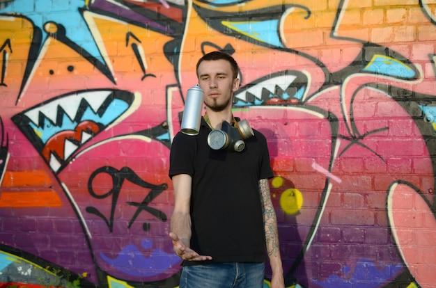 Jovem grafiteiro com máscara de gás no pescoço jogar sua lata de spray contra colorido grafite rosa