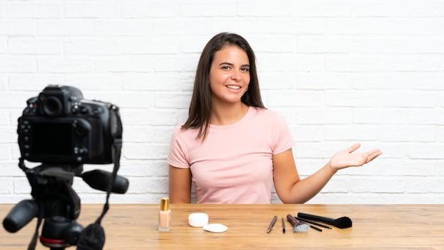 Jovem, gravando um vídeo tutorial segurando copyspace imaginário na palma da mão