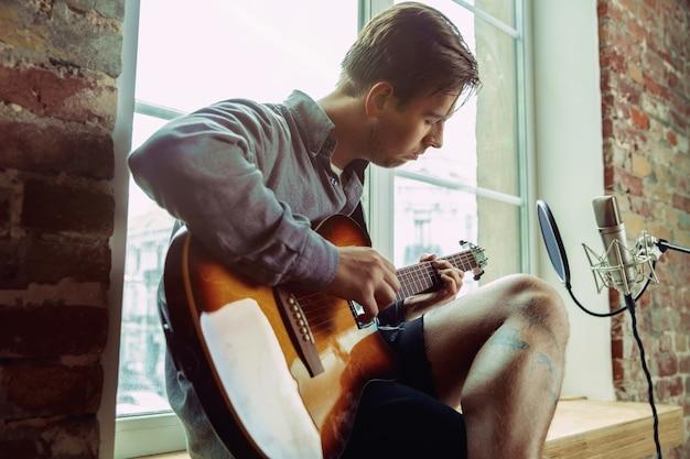 Jovem gravando um videoblog de música, aula ou música em casa, tocando violão ou fazendo um tutorial de transmissão pela internet enquanto está sentado no loft do local de trabalho ou em casa