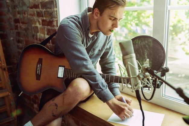 Jovem gravando um videoblog de música, lição em casa ou música, tocando violão ou fazendo um tutorial de transmissão de internet enquanto está sentado no local de trabalho ou em casa. conceito de hobby, música, arte e criação.