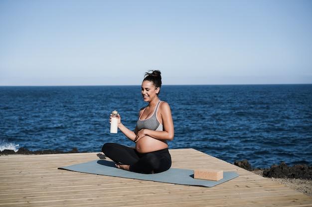 Jovem grávida bebendo água enquanto pratica ioga ao ar livre - foco no rosto