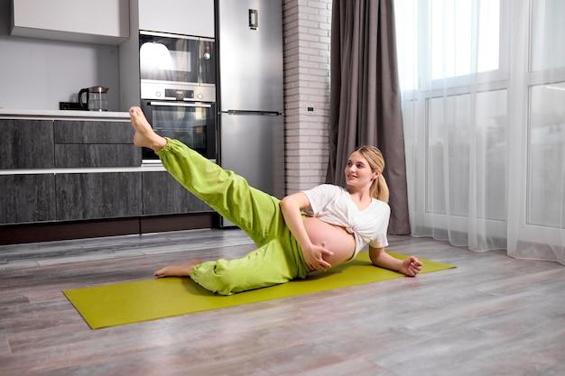 Jovem grávida com a barriga nua levantando uma perna, fazendo exercícios no chão em um colchonete, esporte e ioga para gestantes
