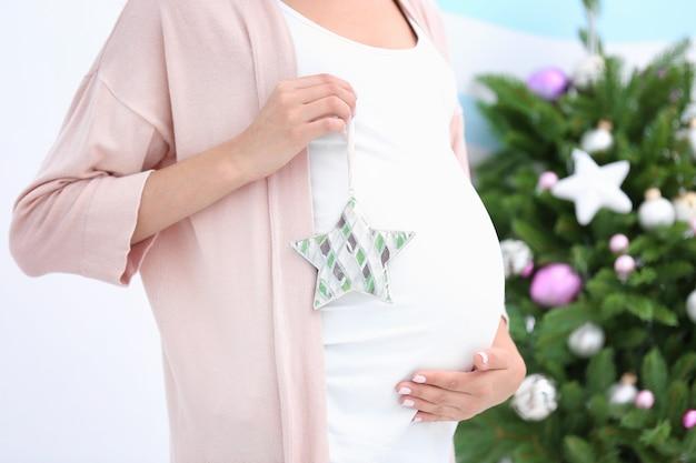Jovem grávida com decoração de natal em casa