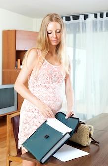 Jovem grávida com documento em papel na sala de estar