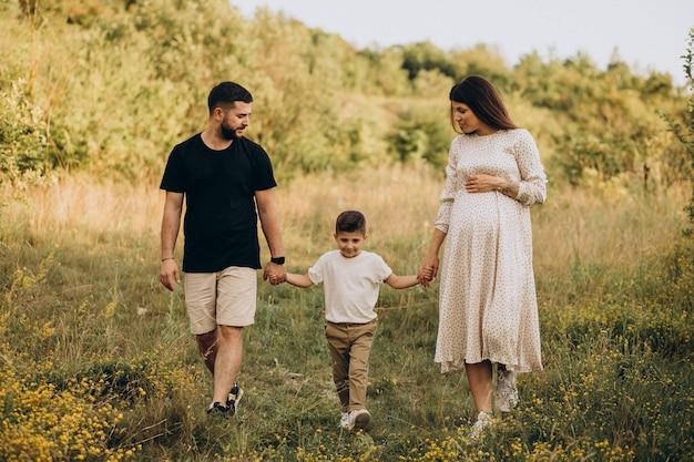 Jovem grávida com marido e filho em uma floresta