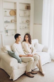 Jovem grávida com o marido a aninhar-se em casa