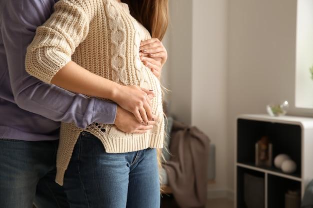 Jovem grávida com o marido em casa