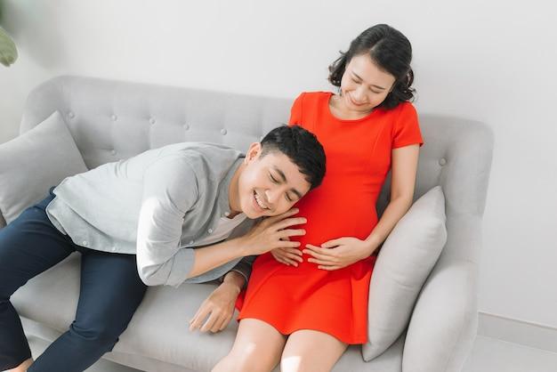 Jovem grávida com o marido esperando o bebê
