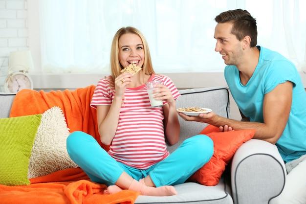 Jovem grávida com o marido no sofá na sala