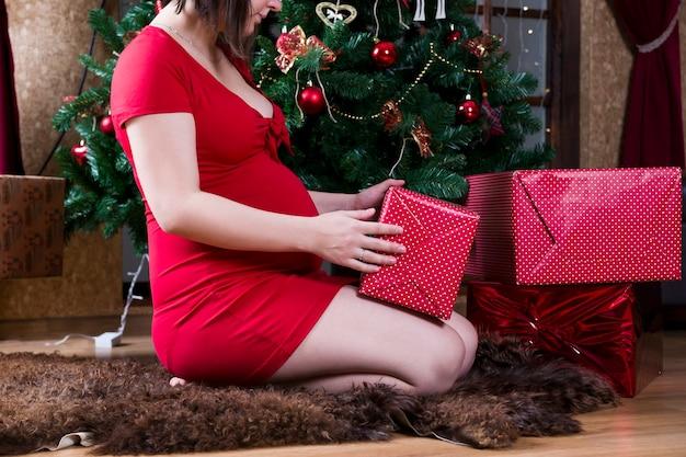 Jovem grávida com um vestido vermelho posando no fundo de um concerto de natal na árvore de natal