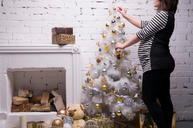 Jovem grávida com uma caixa de presente posando no fundo de uma árvore de natal