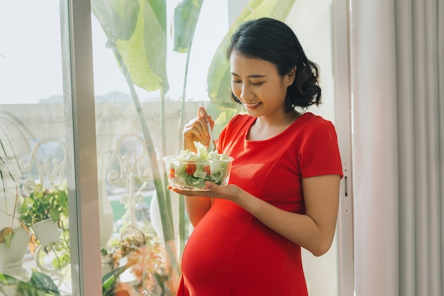Jovem grávida comendo salada de legumes perto da janela de casa