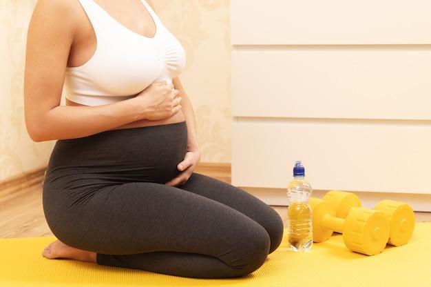 Jovem grávida durante seu treino de fitness em casa