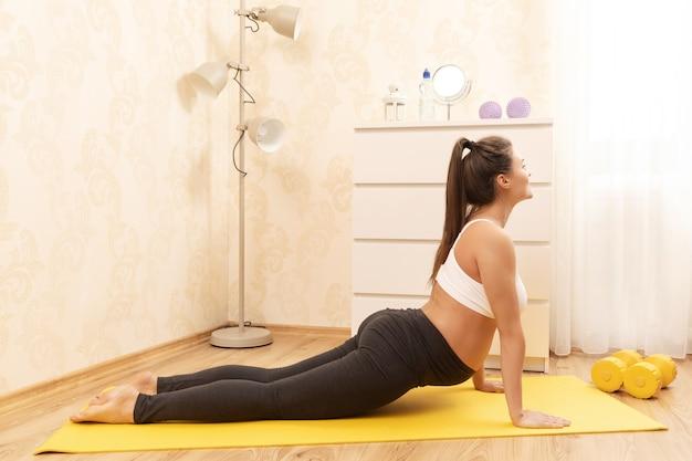 Jovem grávida durante seu treino de ioga em casa