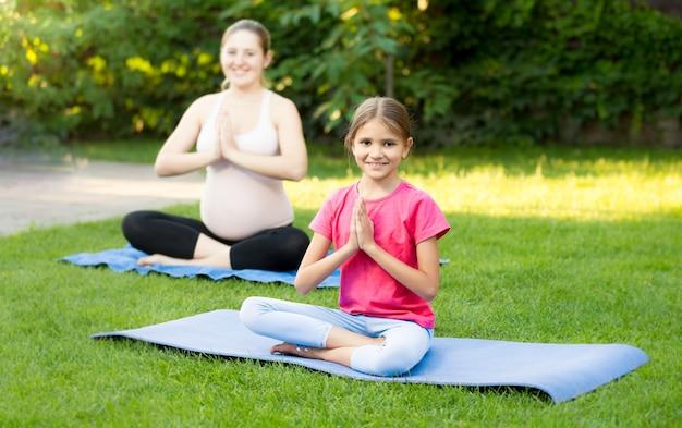 Jovem grávida e linda garota praticando ioga na esteira de ginástica no parque