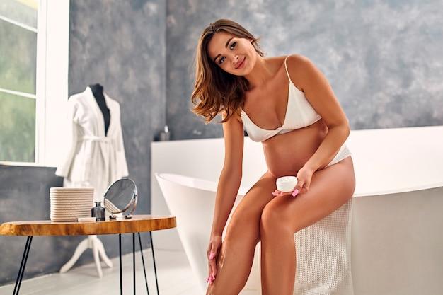 Jovem grávida em cueca branca no banheiro usando hidratante no corpo. rotina matinal. conceito de maternidade.