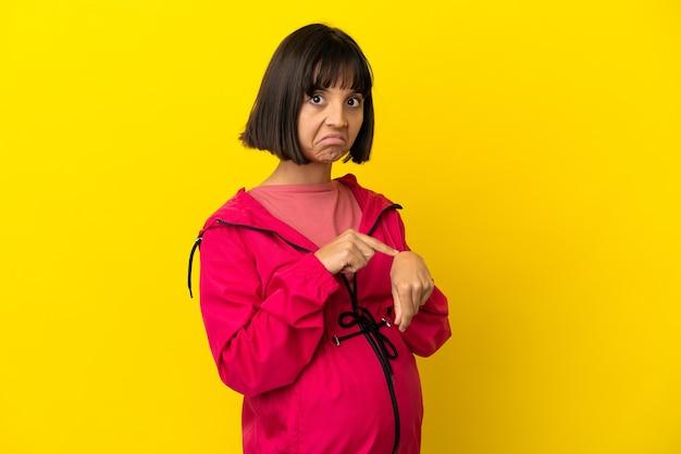 Jovem grávida em fundo amarelo isolado fazendo o gesto de se atrasar