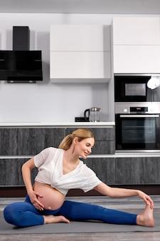 Jovem grávida em roupa esportiva esticando as pernas enquanto está sentada no chão na cozinha