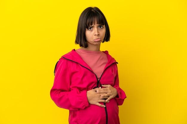 Jovem grávida em um fundo amarelo isolado com uma expressão triste