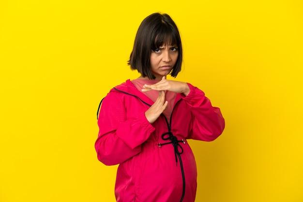 Jovem grávida em um fundo amarelo isolado fazendo um gesto de pausa