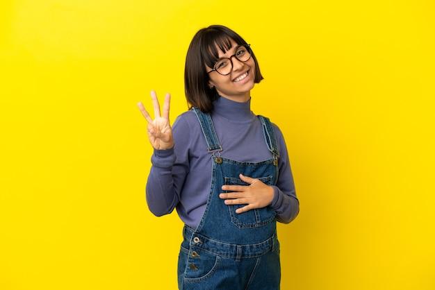 Jovem grávida em um fundo amarelo isolado feliz e contando três com os dedos