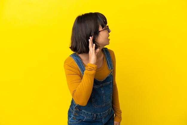 Jovem grávida em um fundo amarelo isolado ouvindo algo colocando a mão na orelha